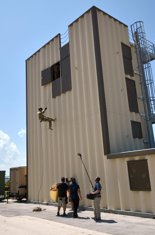 "Tech. Sgt. Ben Domian, a survival, evasion, resistance, and escape specialist with the 920th Rescue Wing, repels down a training tower in front of a Fox TV camera crew June 15, 2016 at Patrick Air Force Base, Fla. The network shot footage of Domian to use for its newest reality show, ""Kicking and Screaming,"" which airs March. 9. Domian is one of 20 contestants on the show. (U.S. Air Force photo/Maj. Cathleen Snow)"