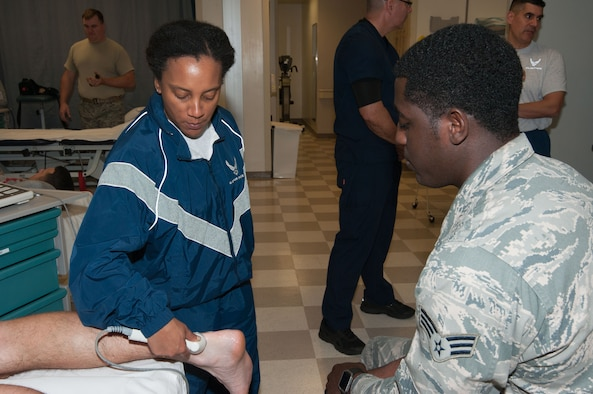 Chief Master Sgt. Erica Shipp, 42nd Air Base Wing command chief, uses a physical therapy technique during her visit to the 42d Medical Operations Squadron,  Feb 21, 2017.  During the visit, medical operations personnel took the command team on a  tour of the Physical Therapy section.  SrA Donald Martin showed Shipp part of what he does for an achilles tendon rehabilitation.   (US Air Force photo by Bud Hancock)