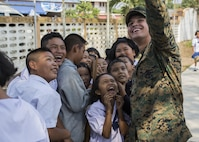 U.S. Marine Corps Cpl. Gabriel Aldrich, with III Marine Expeditionary Force, takes a photo with Thai students during acommunity relations visit to Ban Chong Kapad School in Chanthaburi Province, Thailand, during exercise Cobra Gold, Feb. 20, 2017. Cobra Gold, in its 36th iteration, focuses on humanitarian civic action, community engagement, and medical activities to support the needs and humanitarian interest of civilian populations around the region.