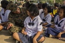 U.S. Marine Corps Sgt. Brittany Alexander, III Marine Expeditionary Force, sits with Thai students during a community relations visit to Ban Chong Kapad School in Chanthaburi Province, Thailand, during exercise Cobra Gold, Feb. 20, 2017. Cobra Gold, in its 36th iteration, focuses on humanitarian civic action, community engagement, and medical activities to support the needs and humanitarian interest of civilian populations around the region.