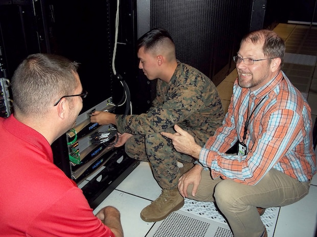 Jason Hessler (left) and Andy Collison (right), Automated Message Handling System support engineers, train a Marine from Marine Corps Installations East G-6 on the Hyper-Converged Infrastructure system Nov. 9, aboard Camp Lejeune, North Carolina. HCI is a virtualization solution that replaces traditional servers, and combines storage and compute functions into a single machine to save cost, energy and space. Marine Corps Systems Command's Information Systems and Infrastructure recently installed the technology at Camp Lejeune, North Carolina, and Camp Pendleton, California, to support Organizational Messaging Service, which is used to send operational and administrative messages across the Corps. (Courtesy photo)