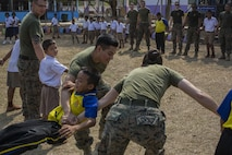 U.S. Marine Corps Lance Cpl. Mia Coleman (right), with Combat Logistics Battalion 4, and Lance Cpl. Alejandro Adame, with 2nd Battalion, 5th Marine Regiment, play games with Thai students during a community relations visit to Ban Chong Kapad School in Chanthaburi Province, Thailand, during exercise Cobra Gold, Feb. 20, 2017. Cobra Gold, in its 36th iteration, focuses on humanitarian civic action, community engagement, and medical activities to support the needs and humanitarian interest of civilian populations around the region.