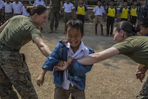 U.S. Marine Corps Lance Cpl. Mia Coleman (right), and Lance Cpl. Alicia Meyer, both with Combat Logistics Battalion 4, play games with Thai students during a Community Relations visit to Ban Chong Kapad School in Chanthaburi Province, Thailand, during exercise Cobra Gold, Feb. 20, 2017. Cobra Gold, in its 36th iteration, focuses on humanitarian civic action, community engagement, and medical activities to support the needs and humanitarian interest of civilian populations around the region.