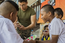 U.S. Marine Corps Lance Cpl. Anthony Hill, with 2nd Battalion 5th Marine Regiment, plays cards with Thai students during a community relations visit to Ban Chong Kapad School in