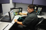 John San Miguel is pictured working with programmable logic controllers as part of the Energy Systems Technology Evaluation Program, or ESTEP, at Space and Naval Warfare Systems Command Systems Center Pacific, Nov., 20, 2013. Navy photo