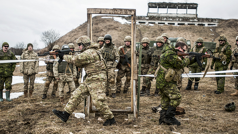 Army Staff Sgt. Uriah Gibson, center left, and a Canadian army engineer show Ukrainian combat training center engineers how to clear a room after using explosives to breach a door during training.