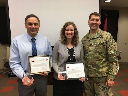 Lt. Col. Stephen Murphy (Right), U.S. Army Corps of Engineers Nashville District commander, presents achievement awards to Eric Crafton and Mary Katherine Keith during a staff meeting Feb. 16, 2017 at the Nashville District Headquarters in Nashville, Tenn. They were two of seven team members who developed a groundbreaking land exchange process that enabled the Nashville District to obtain land needed for a roller compacted concrete berm adjacent to the Center Hill Lake saddle dam at Lancaster, Tenn.