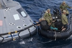 Navy divers and other personnel in a Zodiac boat secure a harness around a test version of the Orion crew module during Underway Recovery Test 5 in the Pacific Ocean off the coast of California, Oct. 28, 2016. Members of the New York Air National Guard's 106th Rescue Wing will participate in a mission in Hawaii designed to test space capsule recovery techniques and equipment, although they will not work with a capsule simulator like this one. Orion is the exploration spacecraft designed to carry astronauts to destinations not yet explored by humans. NASA photo