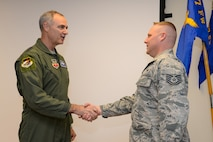 U.S. Air Force Lt. Gen. R. Scott Williams, Commander, CONUS NORAD Region, First Air Force, shakes hands and presents the Commander's Coin to Tech. Sgt. Gabriel Armstrong, New Jersey Air National Guard command post controller from the 177th Fighter Wing on Feb. 16, 2017 at the Atlantic City Air National Guard Base, N.J.  Armstrong, in addition to being recognized for outstanding performance and accomplishments, was also recently named the 2016 CONR 1st AF Command Post Controller of the Year. (U.S. Air Force photo by Master Sgt. Andrew J. Moseley/Released)