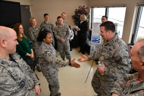 Maj. Gen. Christopher Bence, Expeditionary Center commander, coins Staff Sgt. Cologne Shepherd, 319th Air Base Wing equal opportunity specialist, on Grand Forks Air Force Base, N.D., Feb. 24, 2017. Shepherd was recognized as one of many star performers in the wing by the EC leadership during their visit. (U.S. Air Force photo by Airman 1st Class Elijaih Tiggs)