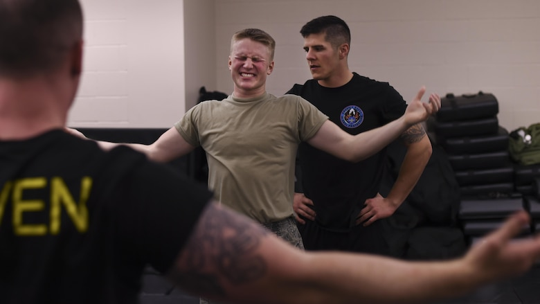 U.S. Air Force Airman 1st Class Timothy Bukovich, 19th Security Forces Squadron patrolman, center, receives motivation from 19th SFS Phoenix Ravens during a rigorous physical training session Feb. 15, 2017, at Little Rock Air Force Base, Ark. The Ravens trained other Airmen to see if they have what it takes to graduate the Air Mobility Command's Phoenix Raven Qualification Course. Raven teams protect aircraft, crews and cargo from criminal and terrorist threats while traveling through airfields where security is either unknown or inadequate. (U.S. Air Force photo/Senior Airman Harry Brexel)