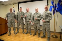 New Jersey Air National Guardsmen from the 177th Fighter Wing show Commander's Coins presented to them by U.S. Air Force Lt. Gen. R. Scott Williams, Commander, CONUS NORAD Region, on Feb. 16, 2017 at the Atlantic City Air National Guard Base, N.J. From right, Tech Sgt. Gabriel Armstrong, Master Sgt. Kevin Allmann, Master Sgt. Bryan O'Neill, Master Sgt. Andrew Eberwine and 177th Command Chief Master Sgt. James McCloskey pose for a group photo. Armstrong was named 2016 CONR 1st AF Command Post Controller of the Year and Allmann was named 2016 CONR 1st AF Security Forces NCO of the Year while O'Neill and Eberwine were lauded for outstanding performance and accomplishments at the Warren Grove Bombing Range and the 177th Fighter Wing Medical Group, respectively.   (U.S. Air Force photo by Master Sgt. Andrew J. Moseley/Released)