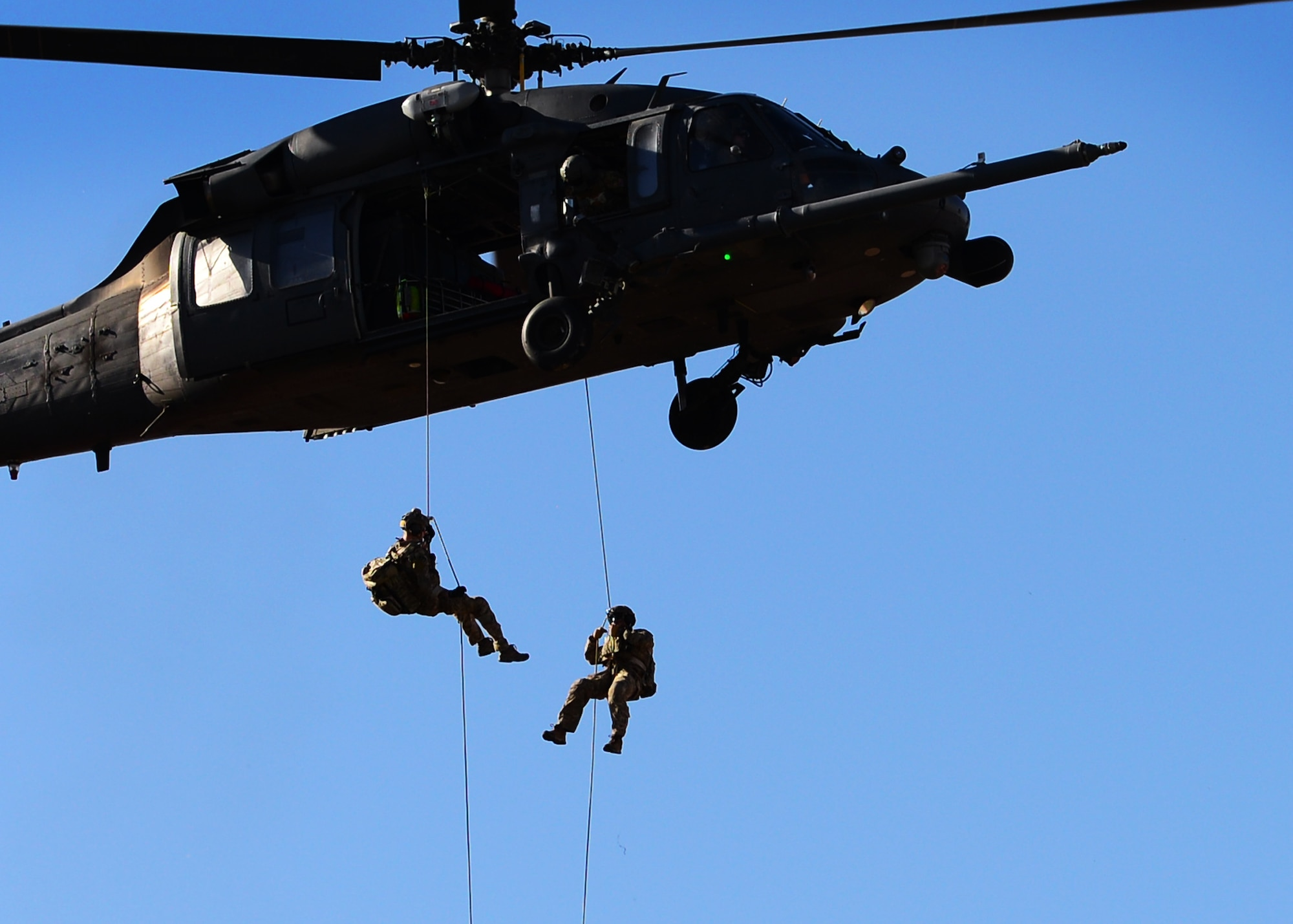 Two U.S. Air Force pararescuemen repel down onto the Warrior Fitness Center field during the 2017 Air Force Warrior Game Trials opening ceremony Feb. 24, 2017 at Nellis Air Force Base, Nev. The pair officially presented Maj. Gen. Peggy Poore, Air Force Personnel Center commander, with the Care Beyond Duty flag. (U.S. Air Force photo by Senior Airman Chip Pons)
