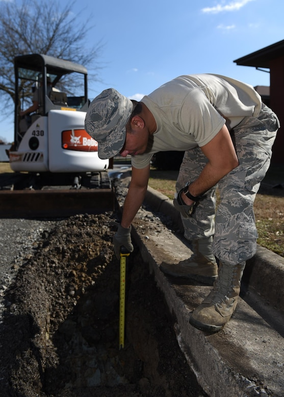 U.S. Air Force Senior Airman Allen Arceo, 19th Civil Engineer Squadron pavement and heavy equipment craftsman, measures the depth of an excavated subbase Jan. 7, 2017, at Little Rock Air Force Base, Ark. Measuring the depth ensures enough material is removed to allow the placement of ballast rock to help strengthen the area of the road. (U.S. Air Force photo by Airman 1st Class Kevin Sommer Giron)