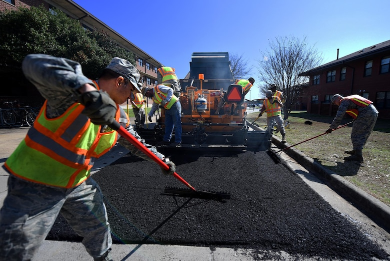 U.S. Air Force Senior Airman Allen Arceo, 19th Civil Engineer Squadron pavement and heavy equipment craftsman, uses a lute tool to spread the asphalt evenly Jan. 7, 2017 at Little Rock Air Force Base, Ark. The lute tool corrects any imperfections left behind by the paver and helps form the edges on the pavement. (U.S. Air Force photo by Airman 1st Class Kevin Sommer Giron)