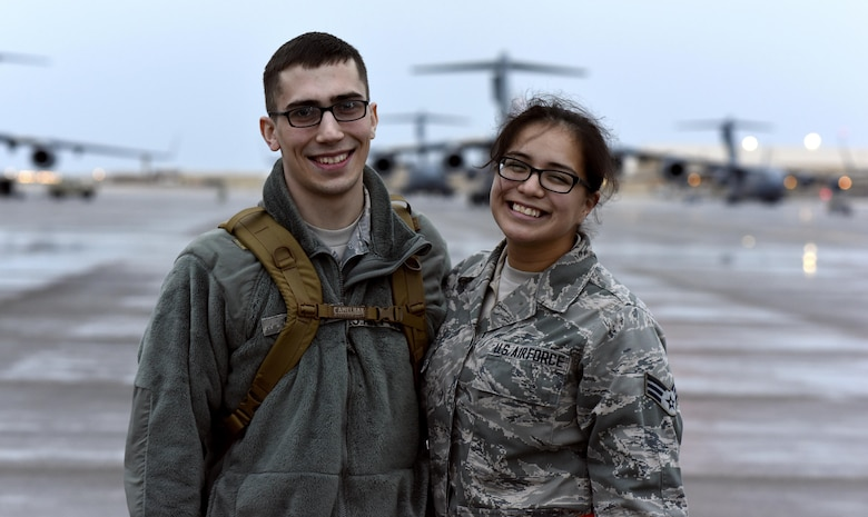 U.S. Air Force Senior Airman Matthew Feigum, a combat crew communications journeyman with the 816th Expeditionary Air Lift Squadron, left, and U.S. Air Force Senior Airman Sylvia Feigum, a combat oriented supply organization journeyman with the 8th Expeditionary Air Mobility Squadron, pose for a photo at Al Udeid Air Base, Qatar, Feb. 16, 2017. The Feigums posed for a photo after Sylvia marshaled in the rotator Matthew arrived on.  (U.S. Air Force photo by Senior Airman Cynthia A. Innocenti)