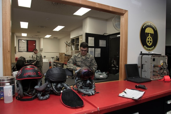 U.S. Air Force Airman 1st Class Dominic Cicci, right, and Senior Airman Coty Buckley, left, both 35th Operations Support Squadron aircrew flight equipment technicians, perform pre-flight and post-flight inspections at Misawa Air Base, Japan, Feb. 8, 2017. The AFE shop oversees pilots' item serviceablility and restocks their uniform with supplies like water and food if needed. (U.S. Air Force photo by Airman 1st Class Sadie Colbert)