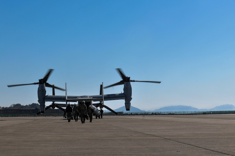 U.S. Marines assigned to the Marine Medium Tiltrotor Squadron 265, Marine Corps Air Station Futenma, Okinawa, Japan, walk toward an MV-22 Osprey at Kunsan Air Base, Republic of Korea, Feb. 2, 2017. The Marine aircrew performed confined area landing patterns as part of their training at Kunsan. (U.S. Air Force photo by Senior Airman Colville R. McFee)