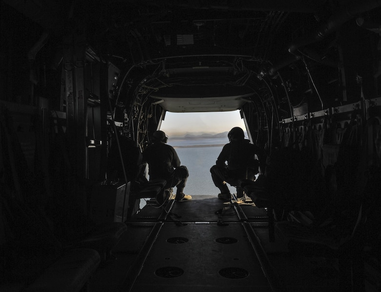U.S. Air Force Senior Airman Michael Hunsaker, 8th Fighter Wing Public Affairs photojournalist, Kunsan Air Base, Republic of Korea, left, and Marine Cpl. Tyler Gartin, Marine Medium Tiltrotor Squadron (VMM) 265, MV-22 Osprey crew chief, surveys the area for other aircraft while flying over Kunsan Air Base, Republic of Korea, Feb. 2, 2017. Gartin provided eyes to the pilots who could not see directly out the rear of the aircraft and Hunsaker photographed the mission. (U.S. Air Force photo by Senior Airman Colville R. McFee)