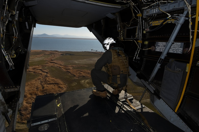 U.S. Marine Corps Cpl. Tyler Gartin, an MV-22 Osprey tiltrotor crew chief assigned to Marine Medium Tiltrotor Squadron (VMM) 265, surveys the area below before it lands at Kunsan Air Base, Republic of Korea, Feb. 2, 2017. Gartin's responsibilities include assisting the pilot by monitoring the area for debris and other aircraft during landing. (U.S. Air Force photo by Senior Airman Michael Hunsaker)