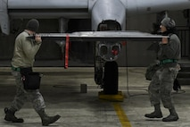 U.S. Air Force Senior Airmen Zachery Wright, left, and Huy Diep, 25th Aircraft Maintenance Unit weapons load crew members, carry a dual rail adapter while loading an A-10 Thunderbolt II during Exercise Beverly Herd 17-1, Feb. 27, 2017, at Osan Air Base, Republic of Korea . The two weapons load crew members were preparing the A-10 for the initial round of missions to be flown during the exercise. (U.S. Air Force photo by Staff Sgt. Victor J. Caputo)