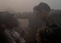 U.S. Air Force Staff Sgt. Daniel Cruz (right) and Staff Sgt. Drake Dinh (middle), 51st Logistics Readiness Squadron traffic management personnel, help a victim in a simulated warehouse fire during Exercise Beverly Herd 17-1, Feb. 27, 2017, at Osan Air Base, Republic of Korea. First responders' evacuated and cared for simulated victims before taking them to a safe zone until medics arrived. (U.S. Air Force photo by Airman 1st Class Gwendalyn Smith)