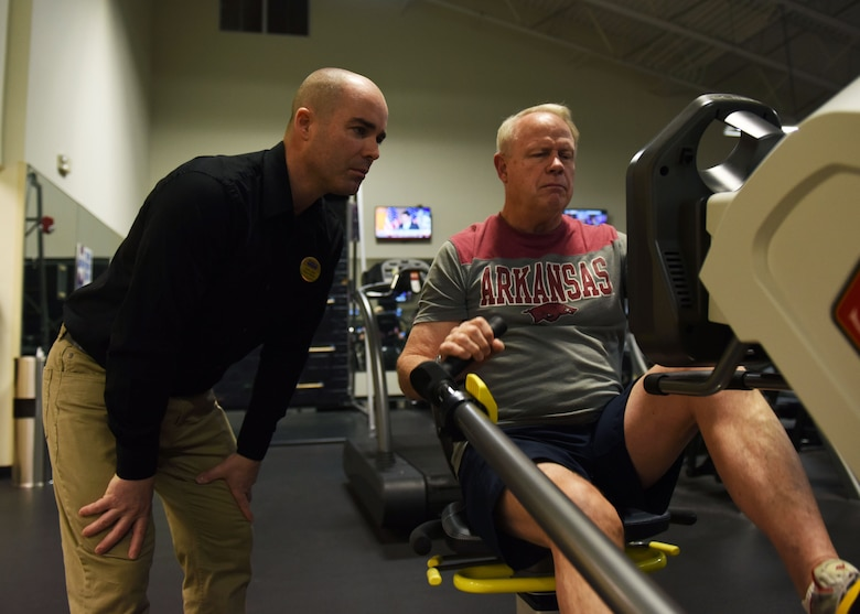 Aaron Leach, left, 19th Force Support Squadron fitness director, trains Michael Smith, retired U.S. Army sergeant first class, on a recumbent elliptical Feb. 2, 2017, at the Fitness Center on Little Rock Air Force Base, Ark. The recumbent elliptical is a new addition to the Fitness Center and creates an adaptive fitness area for those with injuries. (U.S. Air Force photo by Senior Airman Mercedes Taylor)