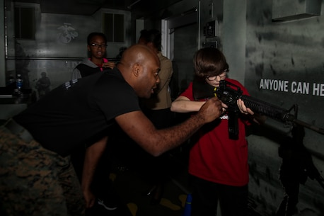 Gunnery Sergeant Maurice S. Sabater, part of the 6th Marine Corps District enhanced marketing vehicle team, assists someone attempting to use the Indoor Simulated Marksmanship Training program at the Central Intercollegiate Athletic Association (CIAA) Fan Fest at the Charlotte Convention Center on Feb. 23, 2017. The Marines take part in the Fan Fest at the CIAA to help spread awareness and inform others of the opportunities the Marine Corps can provide. The Fan Fest assists recruiters by offering them different tools to reach students across the state. (U.S. Marine Corps photo by Lance Cpl. Jack A. E. Rigsby/Released)