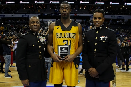 Colonel Jerry Carter, intelligence officer for II Marine Expeditionary Force, left, and Second Lieutenant Yusef Griffin, a communication officer for 1st Marine Logistics Group, present the Marine Corps Excellence in Leadership Award to Enuoma Ebinum of Bowie State University following the men's semifinals game of the Central Intercollegiate Athletic Association (CIAA) championships at the Spectrum Center in Charlotte, N.C., Feb. 24, 2017.  Bowie State University defeated Fayetteville State University 62 to 54. The Marines are present at the Central Intercollegiate Athletic Association championships to spread awareness to student athletes and fans about career and educational opportunities in the Marine Corps. (U.S. Marine Corps photo by Lance Cpl. Jack A. E. Rigsby/Released)