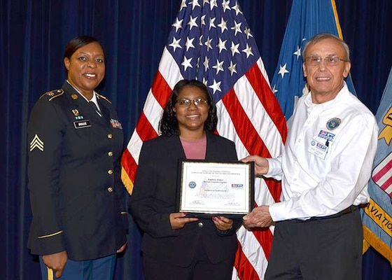 Defense Logistics Agency Information Operations' Audrey Jones (center)  receives the Secretary of Defense, Employer Support of the Guard and Reserve's Patriotic Employer Award from retired Army Lt. Col. Bob Sempek, ESGR Central Virginia Region military outreach volunteer Feb. 21 during a ceremony on Defense Supply Center Richmond, Virginia. Jones was nominated by her employee, Information Technology Specialist Monica Briscoe (left), who is also a sergeant in the Virginia Army National Guard.