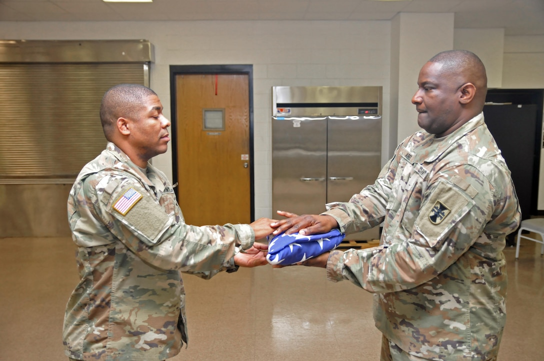 U.S. Army Reserve Soldiers Sgt. 1st Class Jeremy Reed, left, and Sgt. 1st Class Corey Abel, both with the 412th Theater Engineer Command, practice Military Funeral Honors at the Command headquarters in Vicksburg, Miss., Jan. 20, 2017. When the U.S. flag is presented, the point always faces the presenter. They were preparing for a Military Funeral Honors mission the next day.