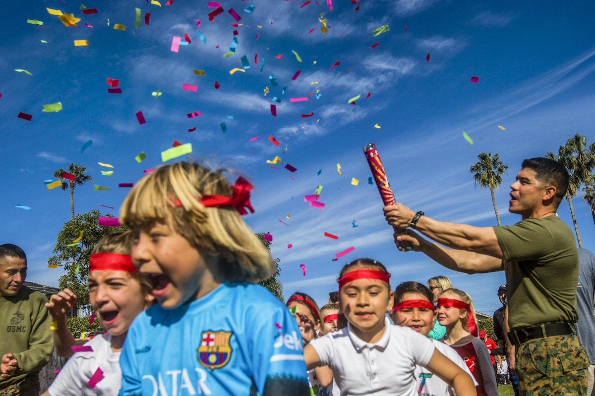A Marine sets off a confetti cannon as children participate in a running event.