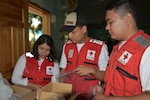 Red Cross volunteers sort vitamins and deworming medication into care bags provided by the preventive medicine team during a Medical Readiness Training Exercise in Corinto, Cortes, Feb. 16, 2017. Red Cross volunteers also facilitated communication between patients and U.S. medical personnel. (U.S. Army photo by Maria Pinel)