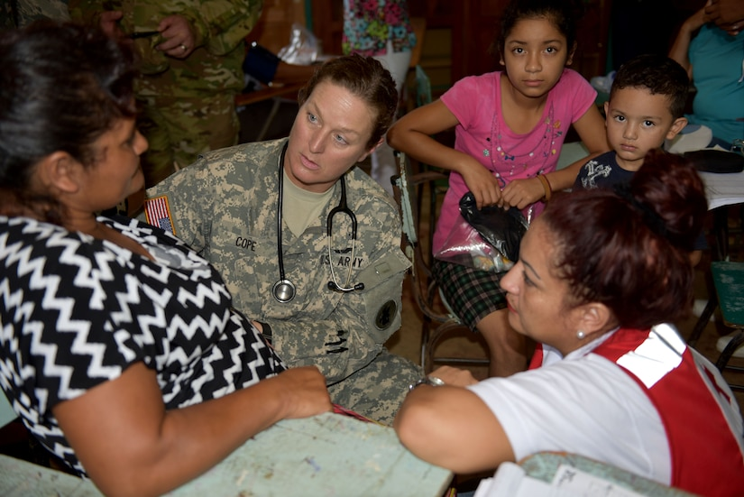 U.S. Army Master Sgt. Nicole Cope, Joint Task Force-Bravo Medical Element, examines a patient during a Medical Readiness Training Exercise in Corinto, Cortes, Feb. 17, 2017. Red Cross volunteers facilitated communication between patients and U.S. medical personnel. (U.S. Army photo by Maria Pinel)