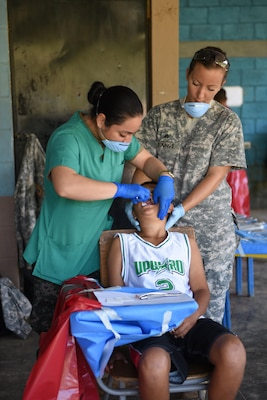 Honduran Army 2nd Lt. Ana Urbina (left) and U.S. Army Sgt. Charissa Youngs, Joint Task Force-Bravo Medical Element, perform a tooth extraction on a young boy during a Medical Readiness Training Exercise in Corinto, Cortes, Feb. 17, 2017.  Besides preparation in the medical field, JTF-Bravo personnel also had the opportunity to develop ties with local health providers, military and other organizations.  (U.S. Army photo by Maria Pinel)
