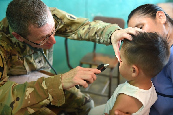 U.S. Army Col. Douglas Lougee, Joint Task Force-Bravo Medical Element commander, examines a young boy during a Medical Readiness Training Exercise in Corinto, Cortes, Feb. 17, 2017. Lougee is also a pediatrician and had the opportunity to participate in a leadership role as well as a provider during the MEDRETE. (U.S. Army photo by Maria Pinel)