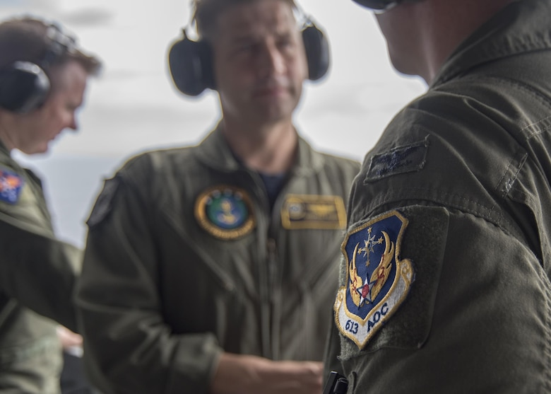 Lt. Cmdr. Jonathan Pohnel, center, Pacific Fleet naval liaison officer, and U.S. Air Force Col. Doug Rice, right, chief of the combat plans division at 613th Air Operations Center (AOC), Joint Base Pearl Harbor-Hickam, Hawaii, discuss flight operations on the aircraft carrier USS Carl Vinson (CVN 70). A four-member team of representatives from the AOC joined the crew of USS Carl Vinson to help bridge the efforts between the AOC and Navy Units while transiting the Pacific area of responsibility. The Carl Vinson Carrier Strike Group is on a regularly scheduled Western Pacific deployment as part of the U.S. Pacific Fleet-led initiative to extend the command and control functions of U.S. 3rd Fleet. U.S Navy aircraft carrier strike groups have patrolled the Indo-Asia-Pacific regularly and routinely for more than 70 years. (U.S. Navy Photo by Seaman Jake Cannady)
