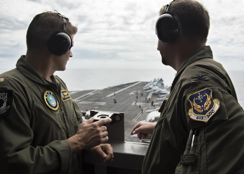 Lt. Cmdr. Jonathan Pohnel, left, Pacific Fleet Liaison Naval Officer, and U.S. Air Force Col. Doug Rice, Chief of the Combat Plans Division at 613th Air Operations Center (AOC), Joint Base Pearl Harbor-Hickam, Hawaii, view flight operations on the aircraft carrier USS Carl Vinson (CVN 70). A four-member team of representatives from the AOC joined the crew of USS Carl Vinson to help bridge the efforts between the AOC and Navy Units while transiting the Pacific area of responsibility. The Carl Vinson Carrier Strike Group is on a regularly scheduled Western Pacific deployment as part of the U.S. Pacific Fleet-led initiative to extend the command and control functions of U.S. 3rd Fleet. U.S Navy aircraft carrier strike groups have patrolled the Indo-Asia-Pacific regularly and routinely for more than 70 years. (U.S. Navy Photo by Seaman Jake Cannady)
