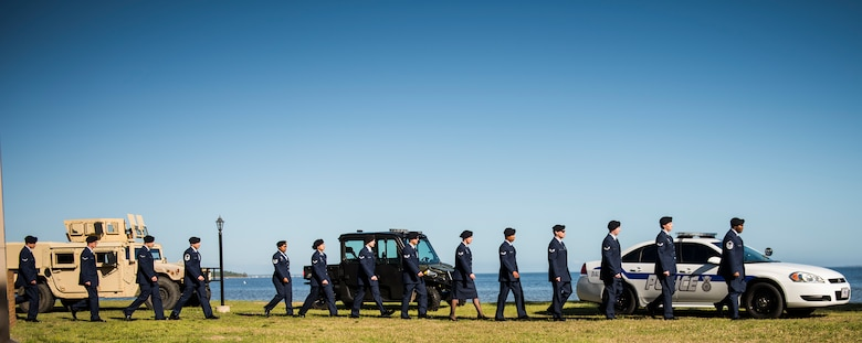A line of 96th Security Forces Squadron Airmen walk by security vehicles during a boat-dedication ceremony Feb. 24 at Eglin Air Force Base, Fla.  The boat was dedicated to Senior Airman Nathan Sartain, a security forces Airman from Pensacola, died in an aircraft crash while deployed in 2015.  The newest patrol boat in the Eglin fleet bears his name to honor his service and sacrifice. (U.S. Air Force photo/Samuel King Jr.)