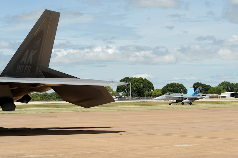 A Royal Australian Air Force F/A-18A/B Hornet taxies past a U.S. Air Force 90th Fighter Squadron F-22 Raptor at RAAF Base Tindal, Australia, Feb. 24, 2017. Twelve F-22 Raptors and approximately 200 U.S. Air Force Airmen are in Australia as part of the Enhanced Air Cooperation, an initiative under the Force Posture Agreement between the U.S. and Australia. (U.S. Air Force photo by Staff Sgt. Alexander Martinez)
