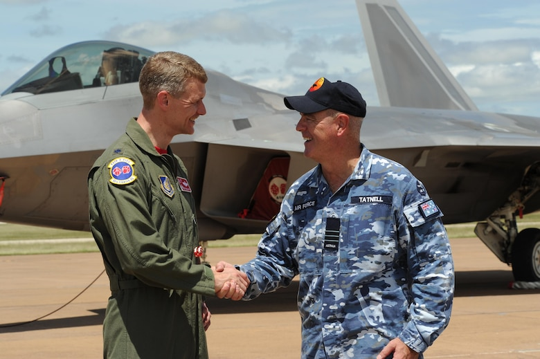 U.S. Air Force Lt. Col. David Skalicky, 90th Fighter Squadron commander, and Wing Commander Andrew Tatnell, Royal Australian Air Force Base Tindal Senior Australian Defence Force Officer, shake hands in front of a U.S. F-22 Raptor at RAAF Base Tindal, Australia, Feb. 24, 2017. Twelve F-22 Raptors and approximately 200 U.S. Air Force Airmen are in Australia as part of the Enhanced Air Cooperation, an initiative under the Force Posture Agreement between the U.S. and Australia. (U.S. Air Force photo by Staff Sgt. Alexander Martinez)