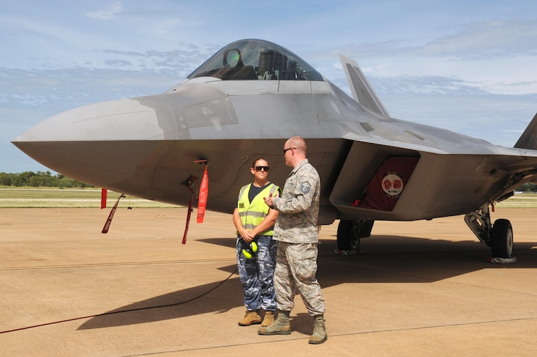 Royal Australian Air Force Leading Aircraft Woman Sarah Ellis, 17 Squadron, and U.S. Air Force Master Sgt. Brenden Bumbert, 90th Aircraft Maintenance Unit, discuss safety points and procedures regarding the F-22 Raptor at RAAF Base Tindal, Australia, Feb. 24, 2017. Twelve F-22 Raptors and approximately 200 U.S. Air Force Airmen are in Australia as part of the Enhanced Air Cooperation, an initiative under the Force Posture Agreement between the U.S. and Australia. (U.S. Air Force photo by Staff Sgt. Alexander Martinez)