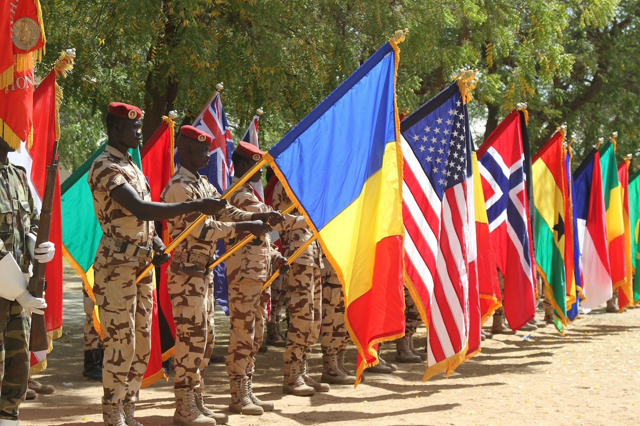 Chadian soldiers raise the flags of partner nations participating in Flintlock 17 during the opening ceremony Feb. 27, 2017. Flintlock is an annual special operations exercise involving more than 20 nation forces that strengthens security institutions, promotes multilateral sharing of information, and develops interoperability among partner nations in North West Africa. Army photo by Staff Sgt. Terrance Payton