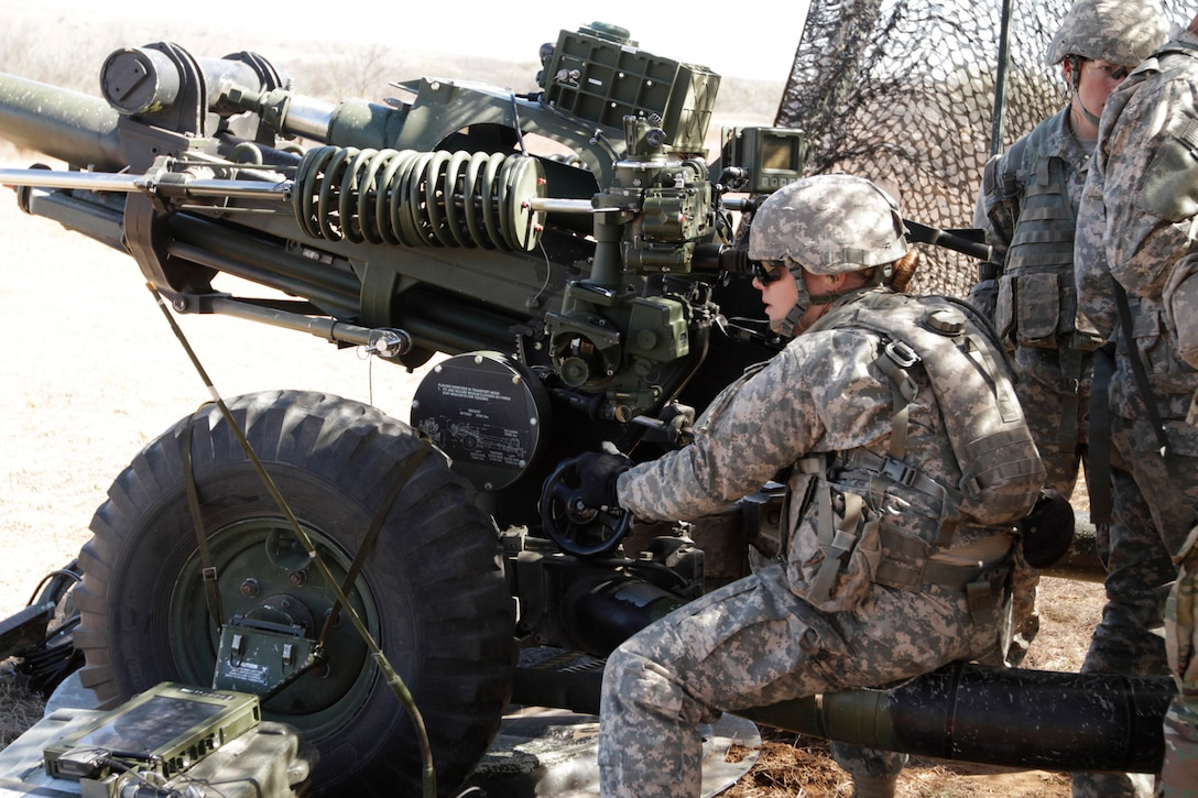 Army Pfc. Katherine Beatty takes her turn at the M119A3 howitzer
