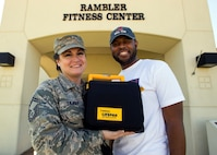 Senior Master Sgt. Brandy Sharp poses for a photo in front of the Rambler Fitness Center on Joint Base San Antonio-Randolph, Texas, with Master Sgt. Ernest Winston and the exact automated external defibrillator she used to save his life. Sharp is the 359th Medical Support Squadron superintendent; Winston is a 359th Medical Group medical technician. (U.S. Air Force photo/Staff Sgt. Kevin Iinuma)