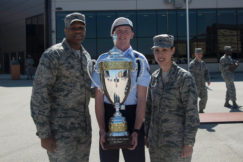 The trophy for first place in the 37th Training Wing Drill Down Invitational is awarded to a representative from the 59th Training Group drill team, by Col. Roy Collins, 37th TRW commander, and Col. Bridget Gigliotti, 37th Training Group commander, at the Pfingston Reception Center at Joint Base San Antonio-Lackland, Texas, Feb. 25, 2017. The 59th Training Group drill team traveled from Joint Base San Antonio-Fort Sam Houston to JBSA-Lackland for the 37th TRW Drill Down Competition.