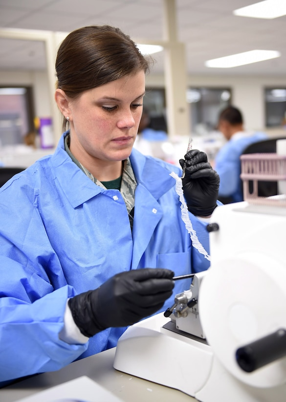 Staff Sgt. Katie Manfred, a 959th Clinical Support Squadron histology technician, cuts a block of tissue sample for testing at the San Antonio Military Medical Center, Joint Base San Antonio-Fort Sam Houston, Jan. 13, 2017. The pathology laboratory serves as a hub for sample testing; the staff receives and processes tissue samples from more than 90 military treatment facilities around the world. (U.S. Air Force photo/Staff Sgt. Jerilyn Quintanilla)