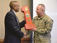 "Retired Sgt. 1st Class Brian Coleman, left, is presented with the ""Big Red One"" Award as a token of appreciation for his service by Fort Riley Garrison Commander Col. John D. Lawrence at Riley's Conference Center Feb. 15. The event observed was Black History Month."