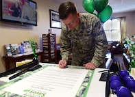 Col. Shawn Thompson, 460th Mission Support Group commander, signs a proclamation for Military Saves Week Feb. 27, 2017, on Buckley Air Force Base, Colo. MSW's goal is to persuade, motivate and encourage military families to practice saving money every month. (U.S. Air Force photo by Airman Jacob Deatherage/Released)