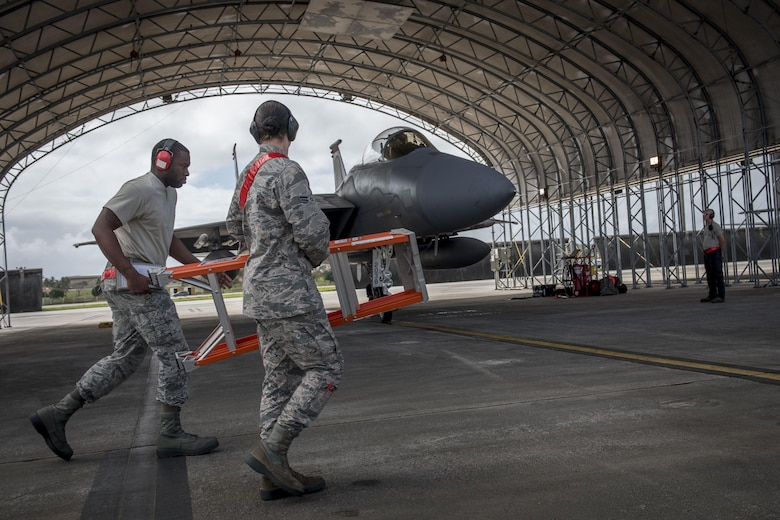 U.S. Air Force weapons Airmen from the 67th Aircraft maintenance Squadron pass an F-15 Eagle during annual exercise Cope North Feb, 23, 2017 on the flightline of Andersen Air Force Base, Guam. During the exercise, weapons teams arm jets one-by-one before they are marshaled out for training missions with aircraft from the Japan Air Self-Defense Force and Royal Australian Air Force. (U.S. Air Force photo by Senior Airman John Linzmeier)